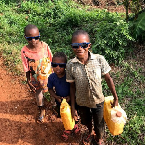 These youngsters interrupted their daily chore of fetching water to receive a pair of sunglasses