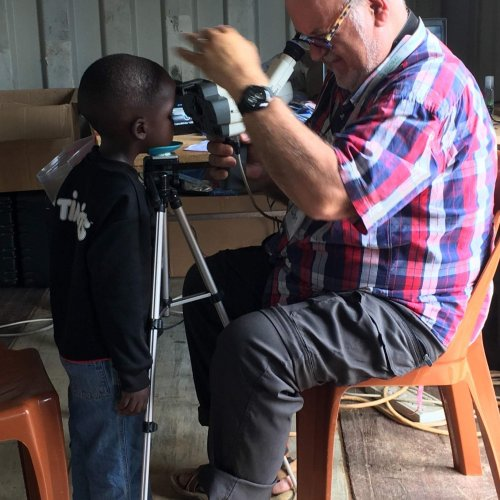 A young boy being check with the auto refractor using an ingenious tripod designed by our ministry partner Rich
